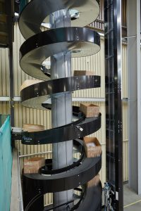 Cartons from the two mezzaine floors are merged on the spiral conveyor and transported to the ground floor